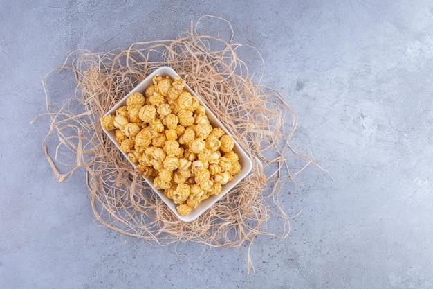 Piccolo piatto di caramelle popcorn su un mucchio di cannucce sulla superficie in marmo