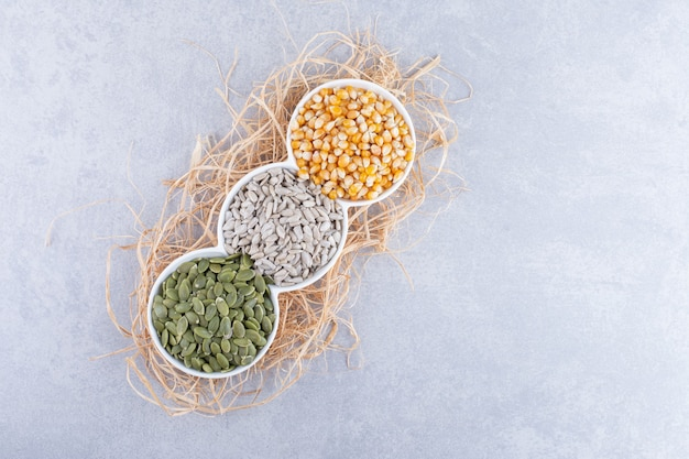 Piccolo piatto con porzioni di chicchi di mais, pepitas e semi di girasole posto su un mucchio di paglia, su una superficie di marmo