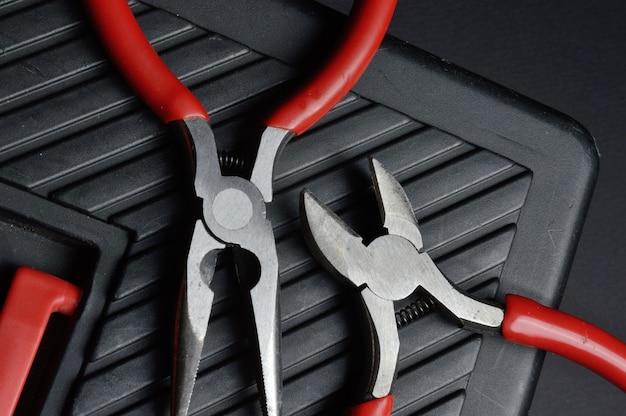 小さなペンチとペンチは閉じた工具箱の上にあります。上からの眺め。