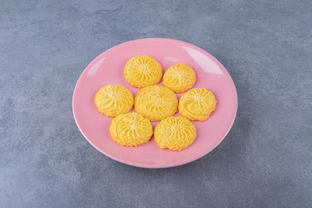 Una piccola porzione di biscotto su un piatto sul tavolo di marmo.