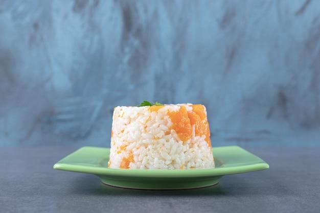 Una piccola porzione di riso alla carota, sulla superficie di marmo.