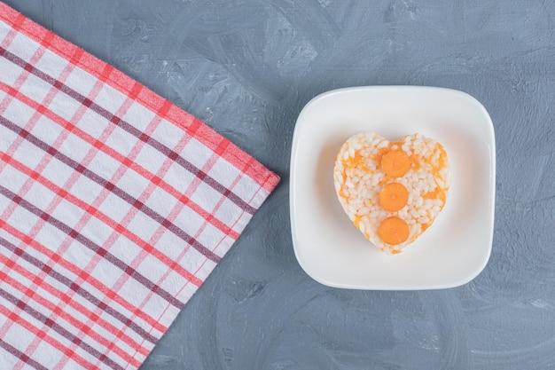 Piccola porzione di riso cotto accanto a un asciugamano su sfondo di marmo.