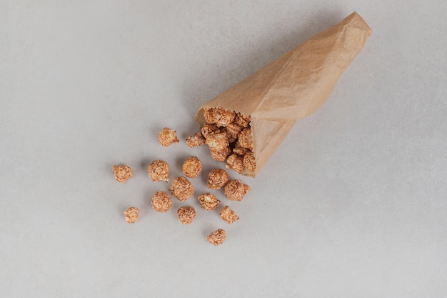 Small portion of popcorn candy in a paper wrapping on marble table.