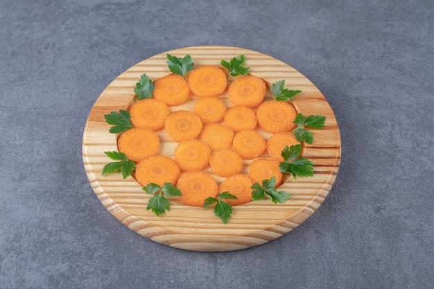 Una piccola porzione di carote e verdure affettate, sulla superficie di marmo.