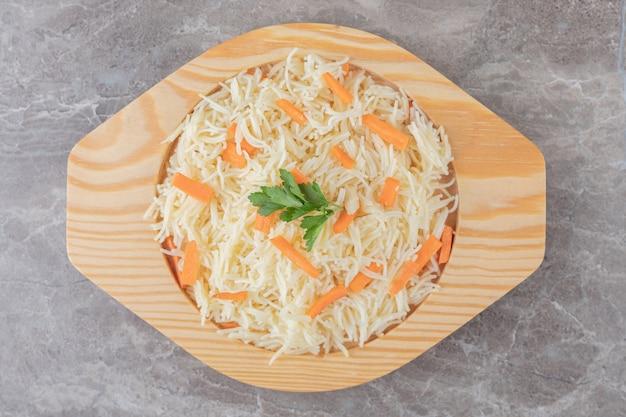 대리석에 채소와 당근을 곁들인 소량의 스파게티.