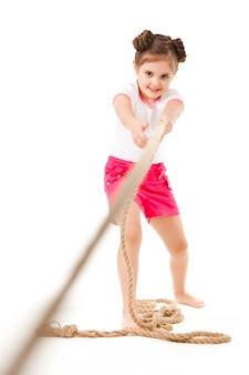 Маленькая позитивная девушка в стильной одежде, стоя, потянув веревку и улыбаясь на белом фоне