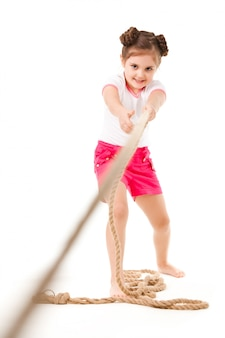 Small positive girl in stylish clothing standing, playing in pulling rope and smiling over white background