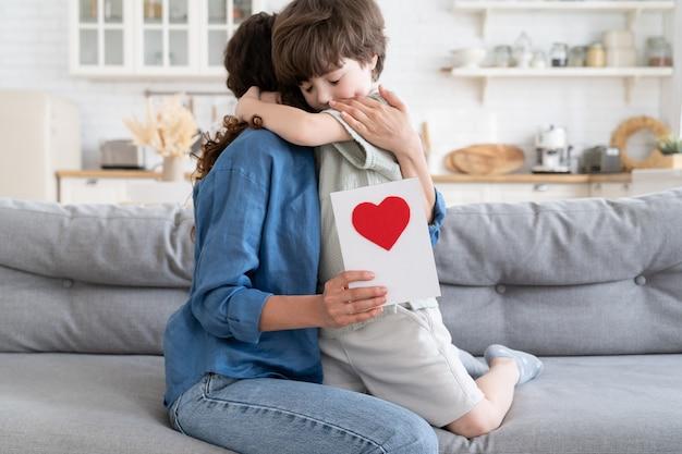 작은 유치원 백인 꼬마 소년은 엄마를 안고 인사말 카드를 들고 있습니다. 어린 아이는 손으로 그린 붉은 마음이 있는 종이 엽서를 선물로 주면서 엄마를 축하합니다. 어머니의 날 또는 생일 축하