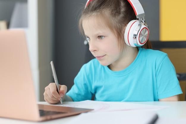 ヘッドフォンで小さな未就学児の女の子がノートパソコンでオンラインで机の勉強に座っています