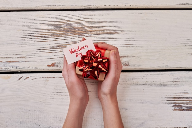 Small present box in hands. valentine's day card and bow. holiday handmade template.