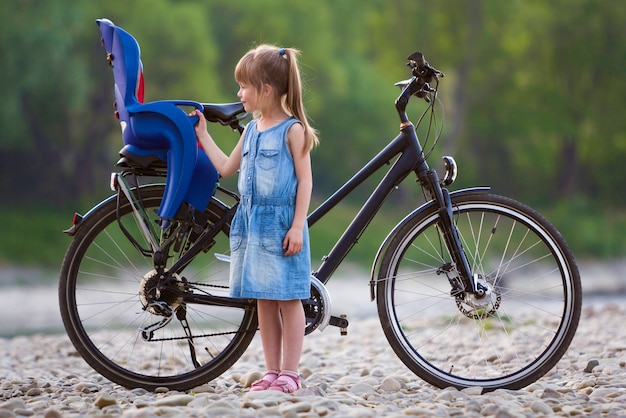 Small pretty blond girl in blue dress standing on pebbles in front of modern bicycle with child seat on blurred green trees background on summer day. active lifestyle and family recreation concept.