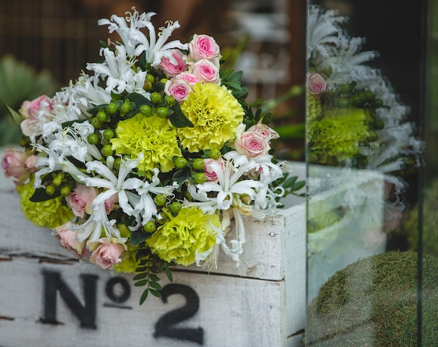 A small and pretty bouquet of colorful flowers inside a white wooden box