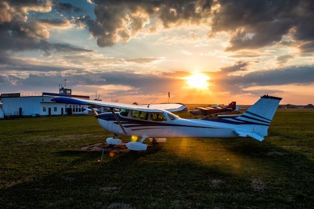 カラフルな夕日を背景に飛行場にある小さな民間航空機
