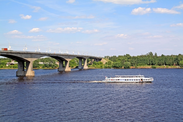 Small promenade motor ship on big river near bridge