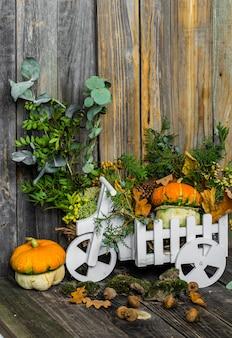 木製の壁に小さなカボチャ、秋