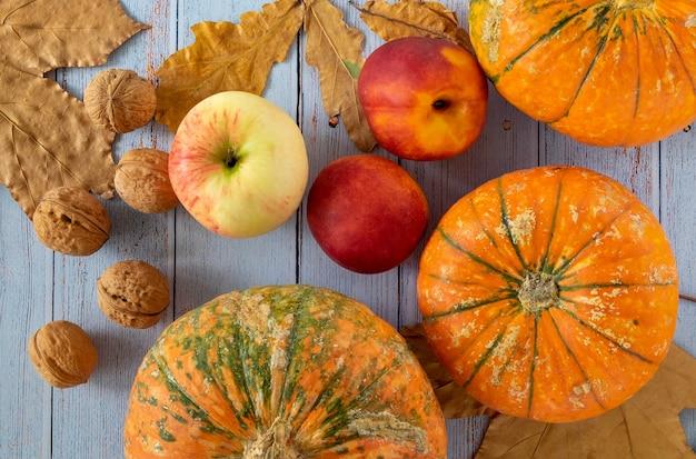 小さなカボチャ、クルミ、ネクタリン、リンゴ、紅葉が木製の背景に配置されています