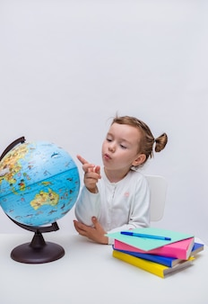 A small pupil sits at a table with textbooks and points at a globe on a white isolated background.vertical orientation