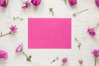 Маленькие фиолетовые цветы с бумагой на столе