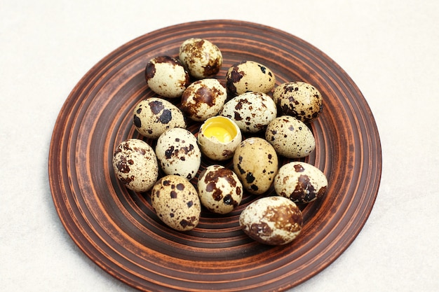 Small quail eggs in a clay plate on light stone background.