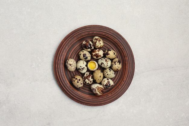 가벼운 돌 테이블에 점토 접시에 작은 메추라기 알