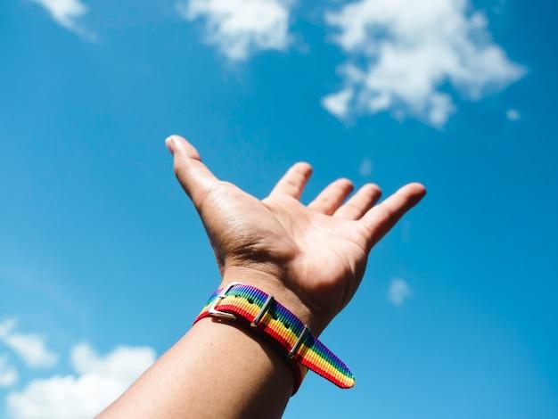 青空の背景に身振りで示す自由とゲイの人々の手首に小さなレインボーフラッグベルト。プライドカラーとレインボーフラッグストリップを備えたlgbtのコンセプト。