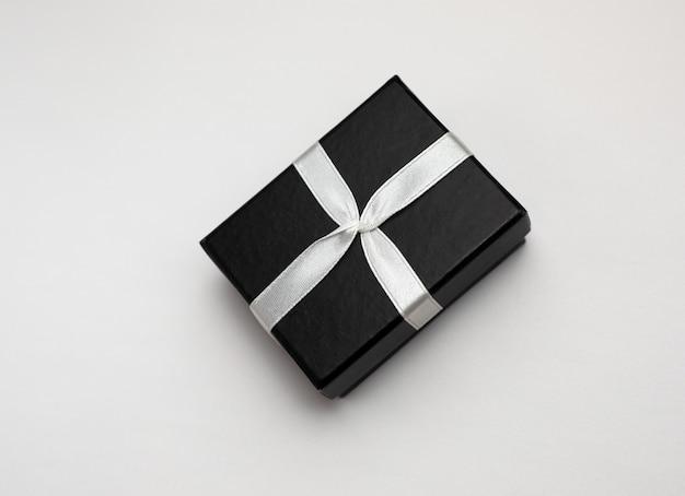 Маленькая прямоугольная черная подарочная коробка на белом фоне