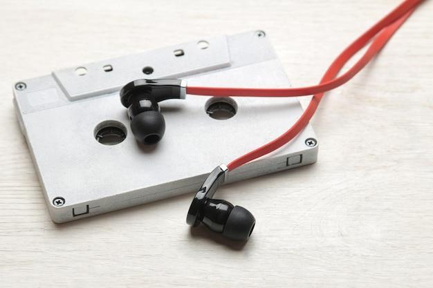 흰색 나무 배경에 작은 빨강 검정 헤드폰과 오디오 카세트. 확대