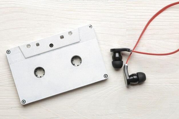 흰색 나무 배경에 작은 빨강 검정 헤드폰과 오디오 카세트. 평면도