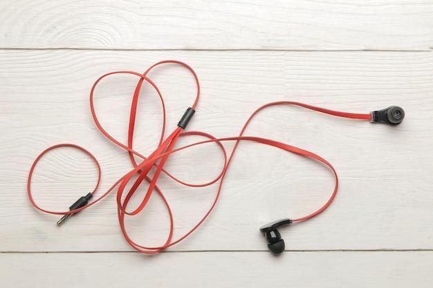흰색 나무 바탕에 스마트폰용 작은 빨강 검정 헤드폰. 평면도