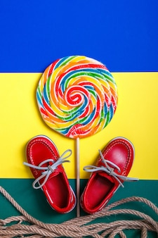 Small red boat shoes near big multi-colored lollipop and rope on colored.