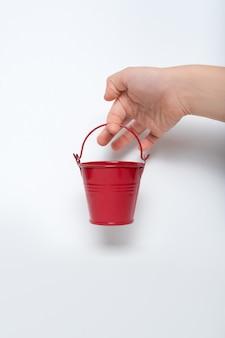 白い壁に子供の手の小さな赤いバケツ。