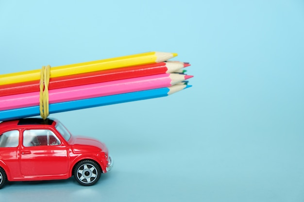 A small red car driven by colored pencils