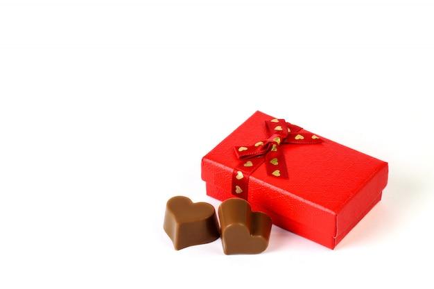 小さな赤いギフトボックスと白い背景のクローズアップの2つのチョコレートの心