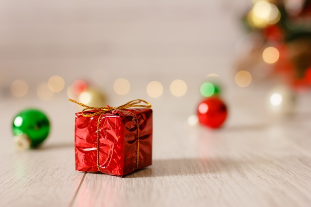 Маленькая красная подарочная коробка в рождественском украшении.