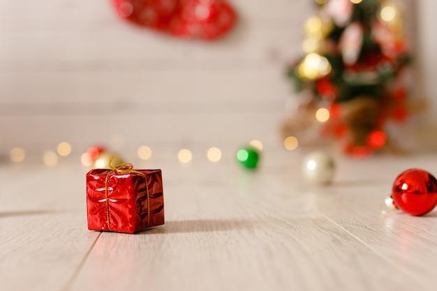 Маленькая красная подарочная коробка в рождественском украшении