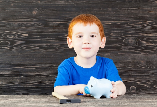 작은 빨간 머리 소년 돼지 저금통과 함께 앉아, 근접 촬영 망치