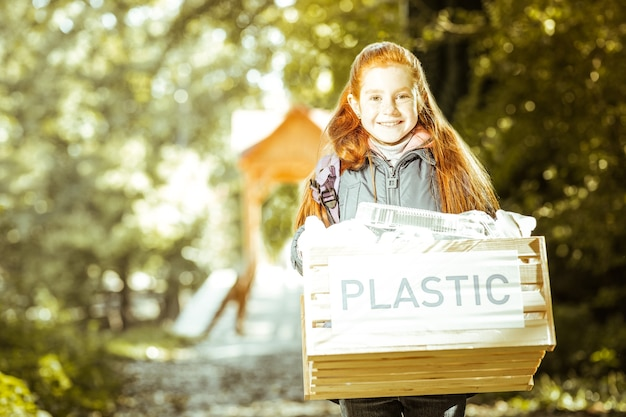 A small red haired girl holding the box of plastic in forest on a good day