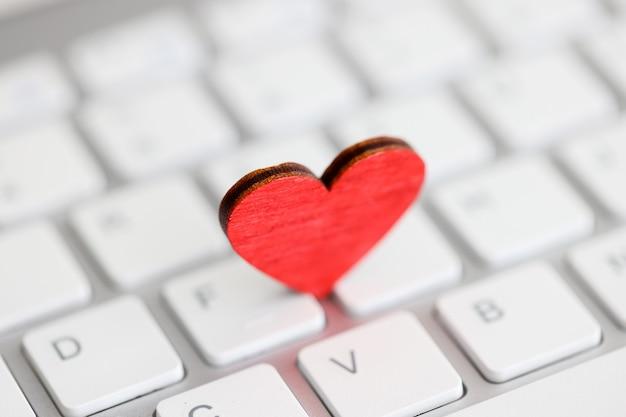 Маленькое красное сердце на клавиатуре компьютера, отправляющее электронное понятие валентинки