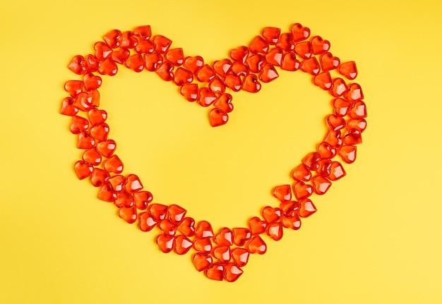 明るい鮮やかな黄色の背景の上に横たわる小さな赤いハート形の透明なキャンディー