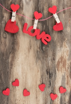 木製の背景に木製の洗濯ばさみにぶら下がっている小さな赤いハートと赤い単語love。コピースペースのあるカード。垂直方向。高品質の解像度