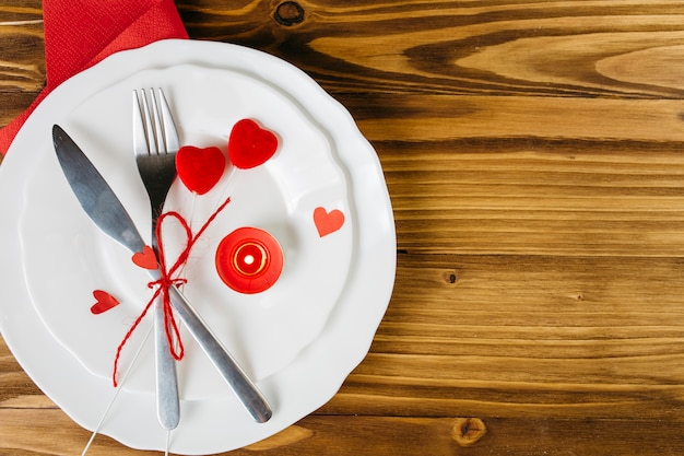 Small red hearts with cutlery on white plate