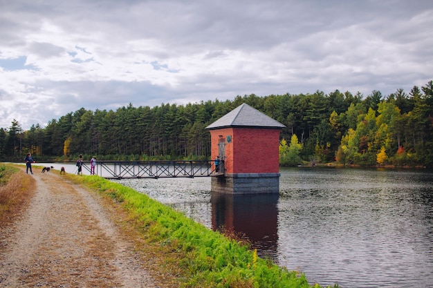 Small red hut built on a river and connected to a bridge with amazing natural scenery