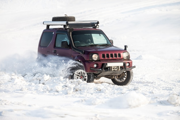 Small red japanese suv riding on snow and snowflakes flying from its wheels