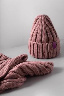 흰색 스카프 jn 회색 배경에 작은 빨간 니트 모자. 털 모자 근접 촬영입니다. 복사 공간