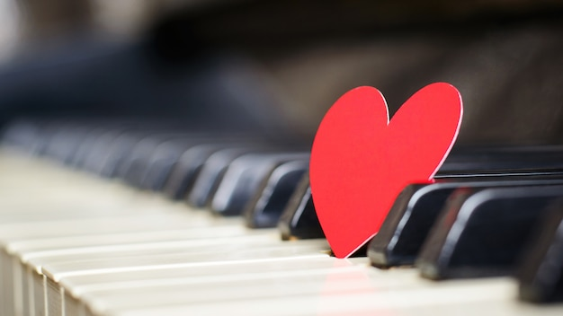 Small red paper heart on piano keys