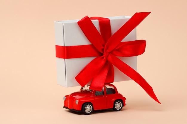 Маленькая красная ретро игрушечная машинка с большим подарком на крыше на розовом