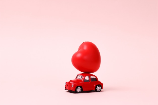 Маленькая красная ретро игрушечная машинка с сердцем на крыше на розовом