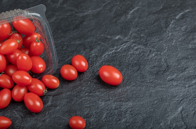 Small red tomato for healthy , on black background. high quality photo