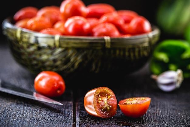 Маленький красный помидор, используемый в качестве кулинарного ингредиента в деревенской кухне, нарезанный ломтиками и кубиками