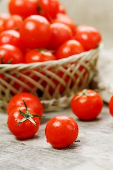 Small red tomatoes in a wicker basket on an old wooden table. ripe and juicy cherry